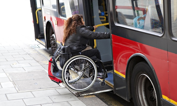 wheelchair user gets on to a bus in London